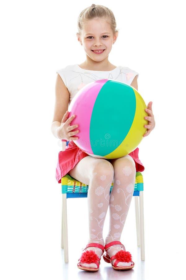 Το κορίτσι κάθεται στην καρέκλα που κρατά στοκ εικόνα