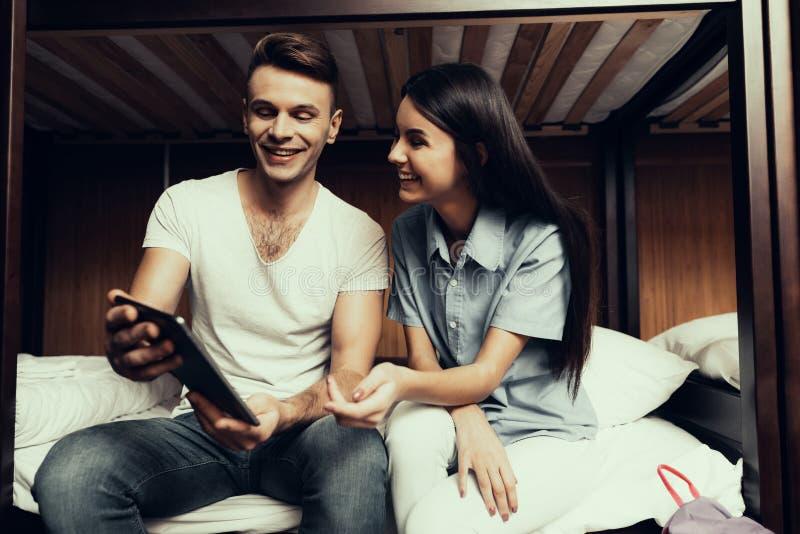 Το κορίτσι και το άτομο κάθονται στα κρεβάτια και εξετάζουν την ταμπλέτα στοκ φωτογραφίες με δικαίωμα ελεύθερης χρήσης