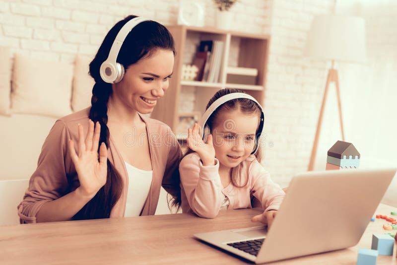 Το κορίτσι και η γυναίκα με τα ακουστικά κοιτάζουν στο lap-top στοκ φωτογραφίες