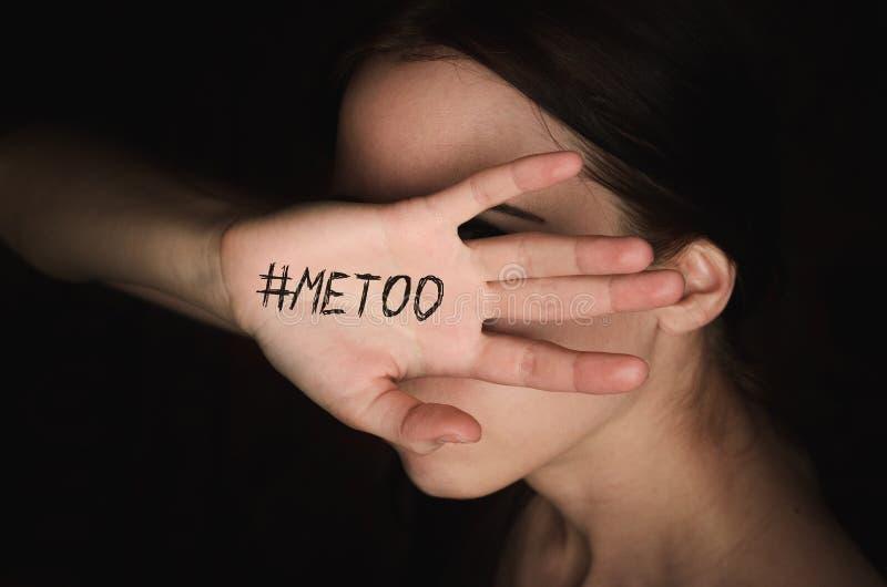 Το κορίτσι καλύπτει το πρόσωπό της με το χέρι με την απομίμηση hashtag ενάντια στην παρενόχληση στοκ εικόνα