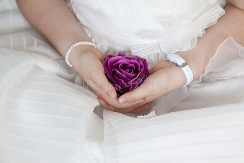 Το κορίτσι κοινωνίας έντυσε στο λευκό με ένα πορφυρό λουλούδι στα handas της στοκ φωτογραφίες