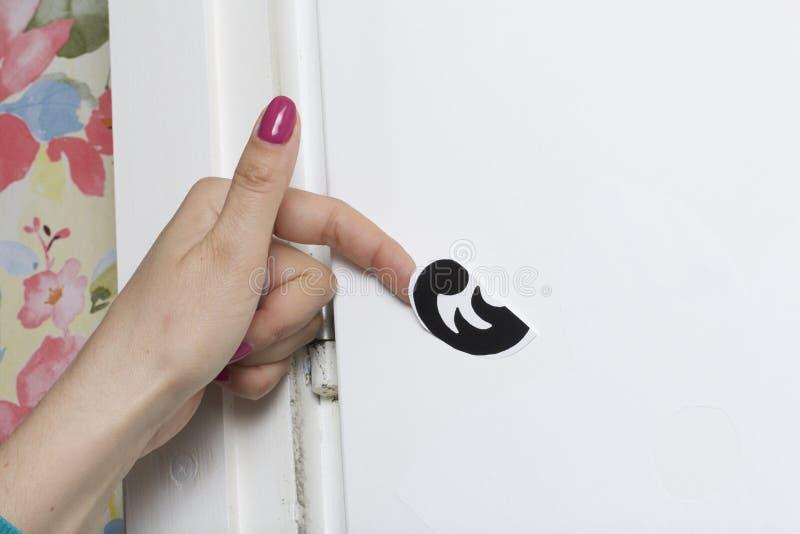 Το κορίτσι κολλά τα αποκόπτω? στοιχεία από το αυτοκόλλητο έγγραφο, για να καλύψει τις ατέλειες της άσπρης πόρτας στοκ εικόνα με δικαίωμα ελεύθερης χρήσης