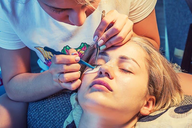 Το κορίτσι κολλά eyelashes στοκ εικόνα με δικαίωμα ελεύθερης χρήσης