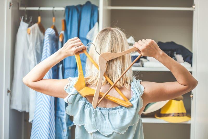 Το κορίτσι κοντά σε μια ντουλάπα με τα ενδύματα δεν μπορεί να επιλέξει τι να φορέσει Η βαριά έννοια επιλογής δεν έχει τίποτα που  στοκ εικόνες με δικαίωμα ελεύθερης χρήσης