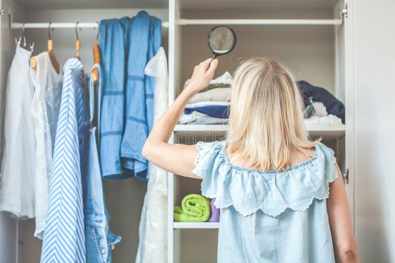 Το κορίτσι κοντά στην ντουλάπα με τα ενδύματα κοιτάζει με μια ενίσχυση - γυαλί που πρέπει να φορέσει Βαριά έννοια επιλογής τίποτα στοκ εικόνες