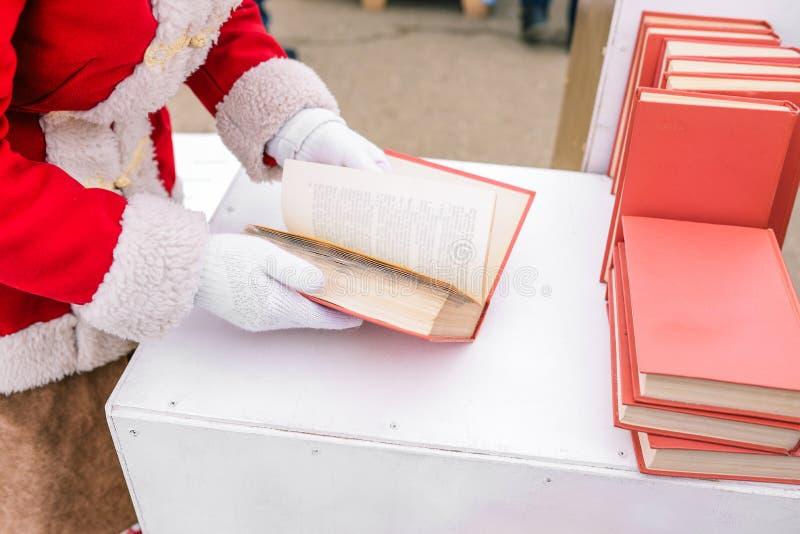 Το κορίτσι κρατά ένα βιβλίο στα χέρια της Ανοιγμένο βιβλίο στους καρκίνους της γυναίκας Βιβλίο που διαδίδεται με τις σελίδες Ένας στοκ φωτογραφίες με δικαίωμα ελεύθερης χρήσης