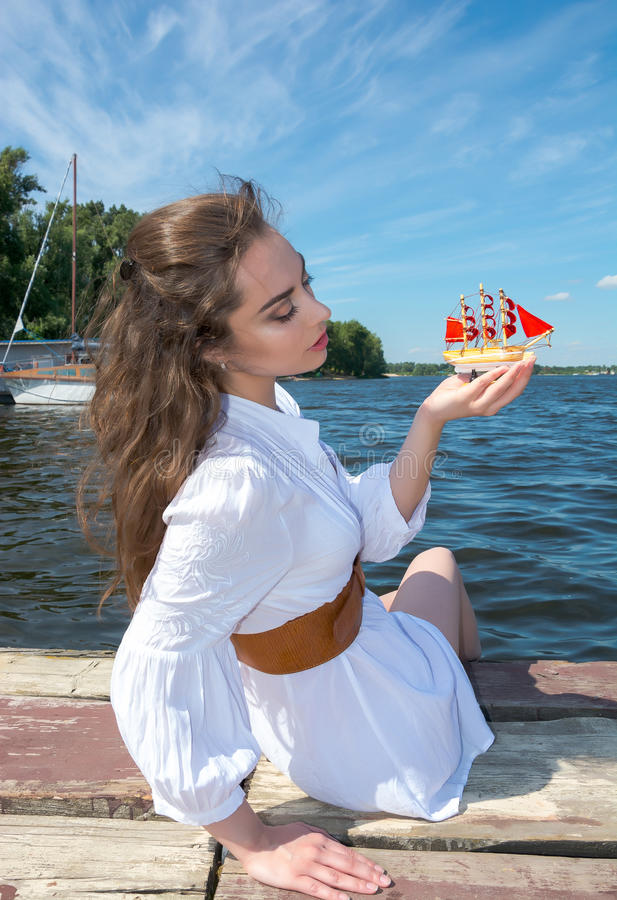 Το κορίτσι κρατά ένα μικρό σκάφος με τα κόκκινα πανιά Σύγχρονο Assol στοκ φωτογραφία