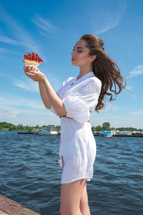Το κορίτσι κρατά ένα μικρό σκάφος με τα κόκκινα πανιά Σύγχρονο Assol στοκ φωτογραφίες