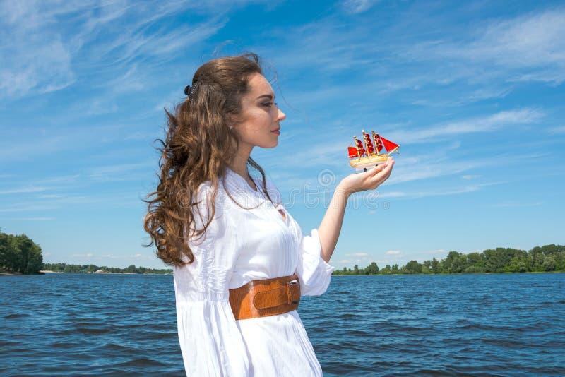 Το κορίτσι κρατά ένα μικρό σκάφος με τα κόκκινα πανιά Σύγχρονο Assol στοκ φωτογραφία με δικαίωμα ελεύθερης χρήσης