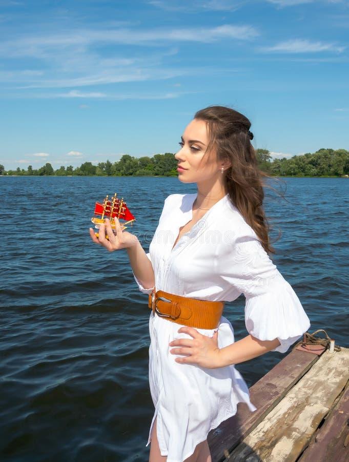 Το κορίτσι κρατά ένα μικρό σκάφος με τα κόκκινα πανιά στοκ φωτογραφίες με δικαίωμα ελεύθερης χρήσης