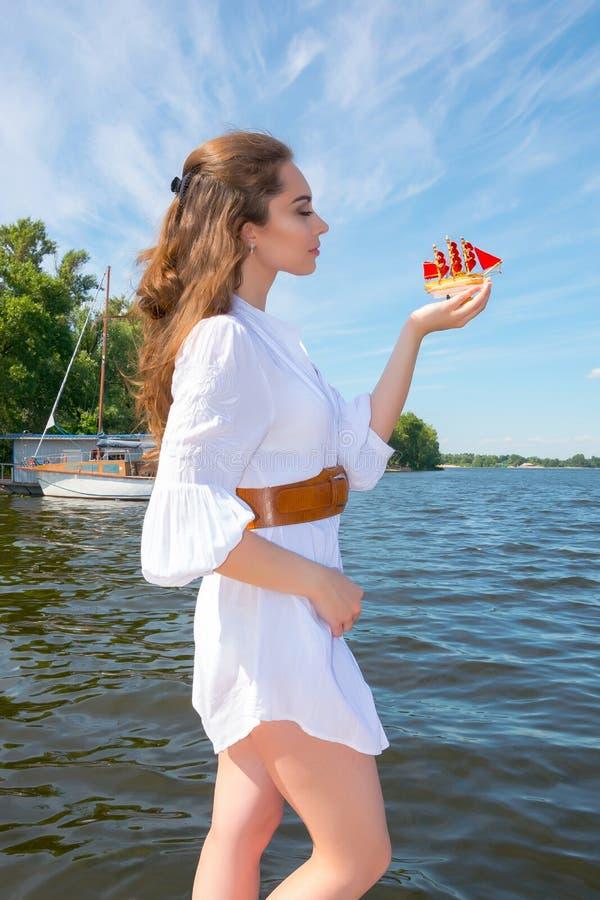 Το κορίτσι κρατά ένα μικρό σκάφος με τα κόκκινα πανιά στοκ εικόνες