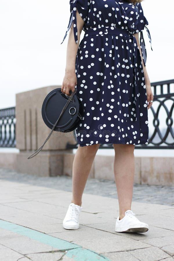 Το κορίτσι κρατά μια μαύρη στρογγυλή τσάντα στο χέρι της και περπατά κάτω από την οδό, η έννοια ενός μοντέρνου συνδυασμού ενδυμάτ στοκ φωτογραφία