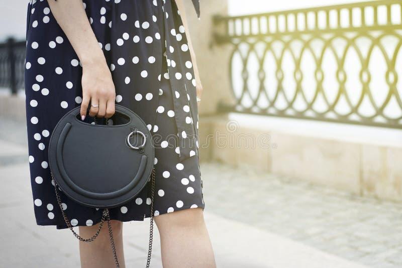 Το κορίτσι κρατά μια μαύρη στρογγυλή τσάντα στο χέρι της και περπατά κάτω από την οδό, η έννοια του μοντέρνου συνδυασμού ενδυμάτω στοκ φωτογραφία με δικαίωμα ελεύθερης χρήσης