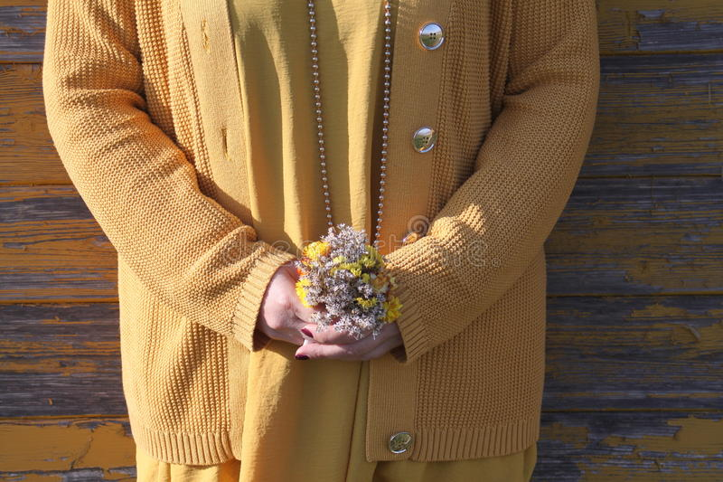 Το κορίτσι κρατά μια μικρή ανθοδέσμη λουλουδιών στοκ εικόνες
