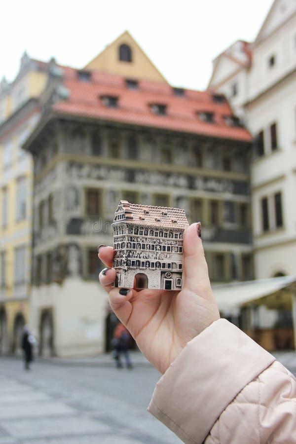 Το κορίτσι κρατά το τσεχικό μικρό σπίτι σπιτιών αναμνηστικών, u Minuty Dum, στο υπόβαθρο εκείνου του πραγματικού σπιτιού, παλαιά  στοκ φωτογραφίες με δικαίωμα ελεύθερης χρήσης