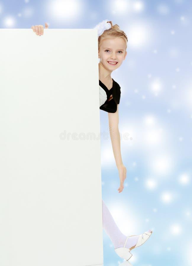 Το κορίτσι κρυφοκοιτάζει έξω από πίσω από το άσπρο έμβλημα στοκ φωτογραφία με δικαίωμα ελεύθερης χρήσης