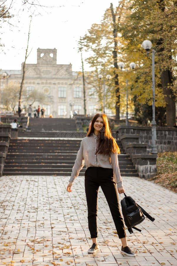 Το κορίτσι με ένα σακίδιο πλάτης στέκεται κοντά στα βήματα που οδηγούν στο πανεπιστήμιο στοκ φωτογραφίες