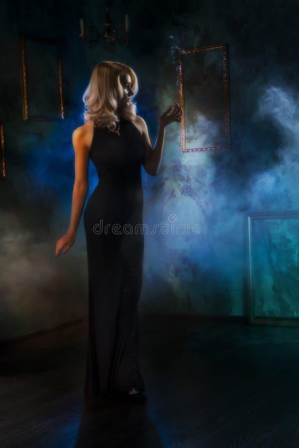 Το κορίτσι με ένα τσιγάρο σε μια θεατρική ομίχλη θολωμένος retrosty στοκ φωτογραφία με δικαίωμα ελεύθερης χρήσης
