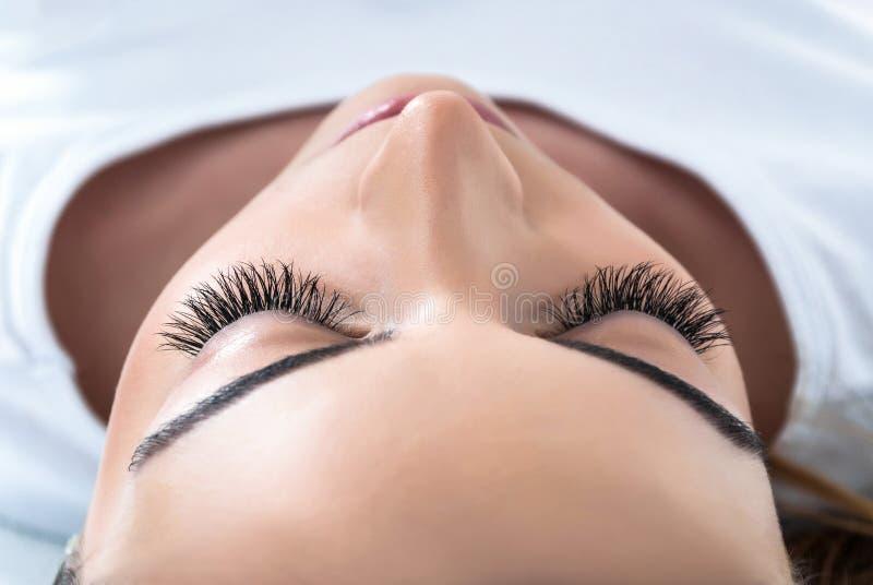 Το κορίτσι με το εκτεταμένο μετάξι eyelashes βρίσκεται σε ένα στούντιο ομορφιάς στοκ εικόνες