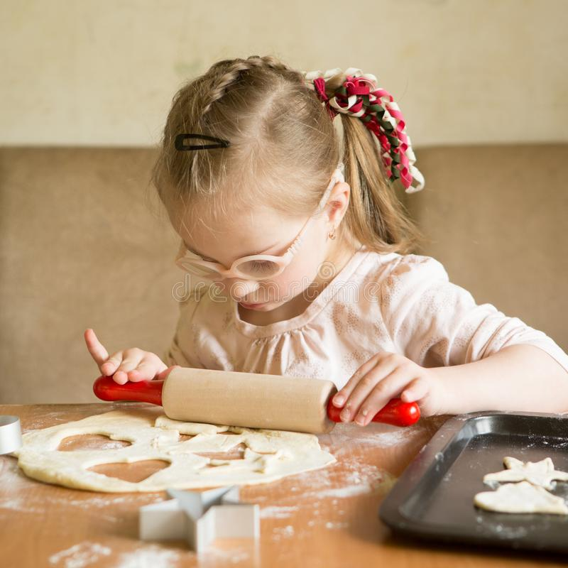Το κορίτσι με το κάτω σύνδρομο κυλά τη ζύμη στο μπισκότο στοκ εικόνες