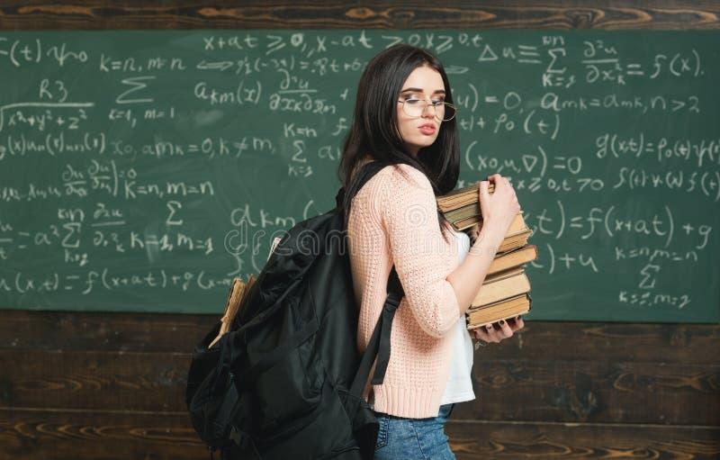 Το κορίτσι με το μεγάλο σακίδιο πλάτης κρατά τα βιβλία σωρών, υπόβαθρο πινάκων κιμωλίας Εργασίες σπουδαστών κοριτσιών για την έρε στοκ εικόνες