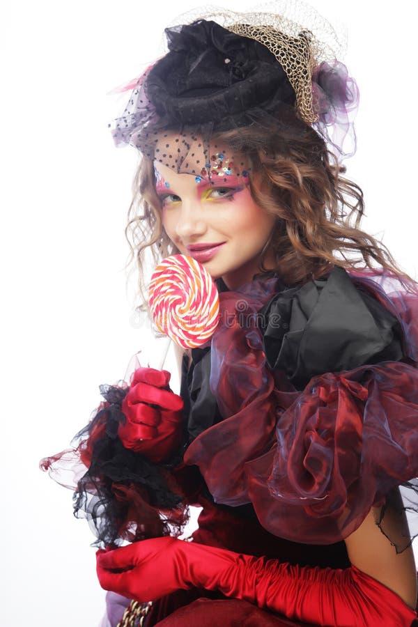 Το κορίτσι με με τη δημιουργική σύνθεση κρατά lollipop στοκ εικόνα