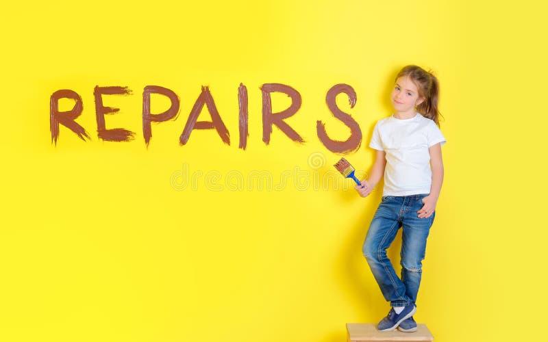 το κορίτσι με μια βούρτσα χρωμάτων στέκεται κοντά στον τοίχο με τις επισκευές επιγραφής στοκ φωτογραφία