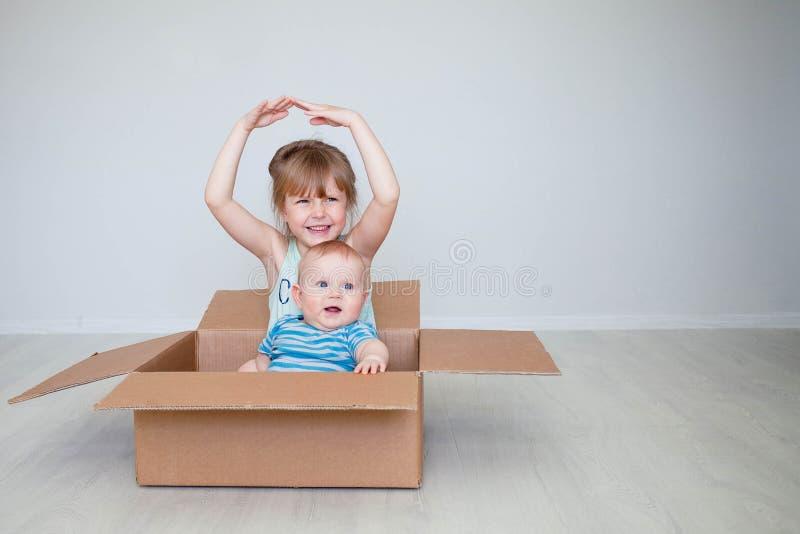Το κορίτσι με το μικρό αδελφό κάθεται σε ένα κιβώτιο, η έννοια της κίνησης αντιπροσωπεύει τα χέρια η στέγη στοκ φωτογραφία