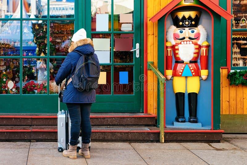 Το κορίτσι με το σακίδιο πλάτης και οι αποσκευές τοποθετούν σε σάκκο στο σπίτι καρυοθραύστης στην αγορά Χριστουγέννων σε Alexande στοκ φωτογραφίες με δικαίωμα ελεύθερης χρήσης