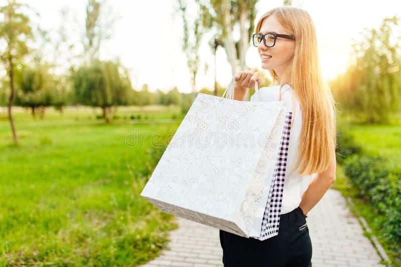 Το κορίτσι με τα γυαλιά, έντυσε σε μια άσπρη μπλούζα, κρατώντας μια αγορά ενώ στο πάρκο στοκ εικόνα