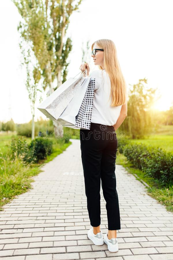 Το κορίτσι με τα γυαλιά, έντυσε σε μια άσπρη μπλούζα, κρατώντας τα purchas στοκ εικόνα