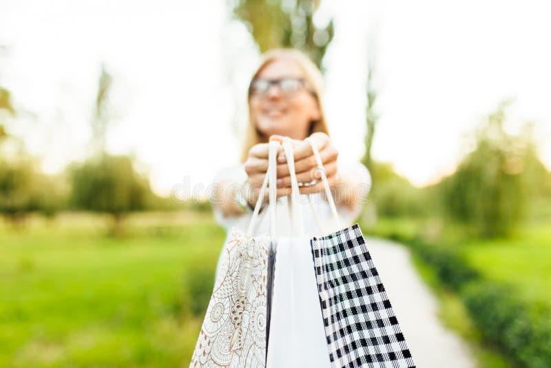 Το κορίτσι με τα γυαλιά, έντυσε σε μια άσπρη μπλούζα, κρατώντας τα purchas στοκ φωτογραφίες