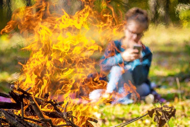 Το κορίτσι με το τηλέφωνο είναι unobtrusively ορατό από την πυρκαγιά και τον καπνό από τη φωτιά το φθινόπωρο στο woods_ στοκ εικόνες με δικαίωμα ελεύθερης χρήσης
