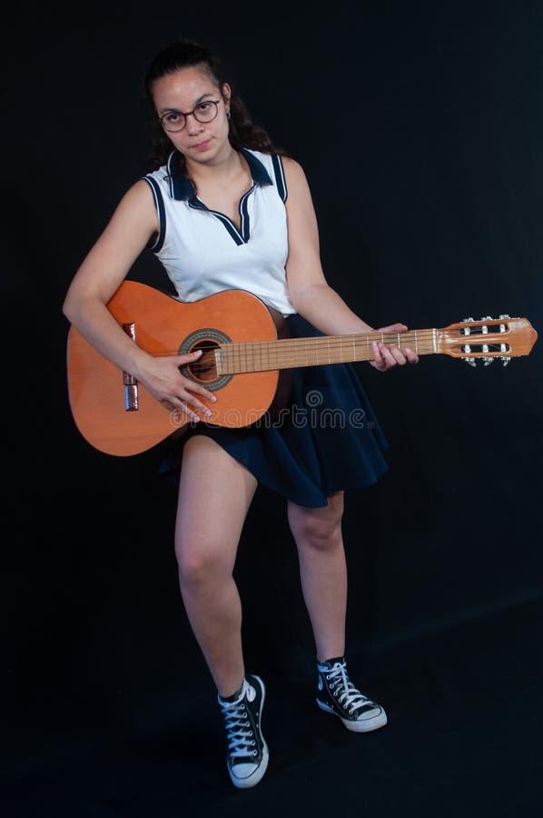 Το κορίτσι με την καφετιά τρίχα, που στέκεται, χαμογελώντας, παίζει την κιθάρα όπως έναν rockstar Διασκεδασμένος φανείτε γυρισμέν στοκ εικόνα