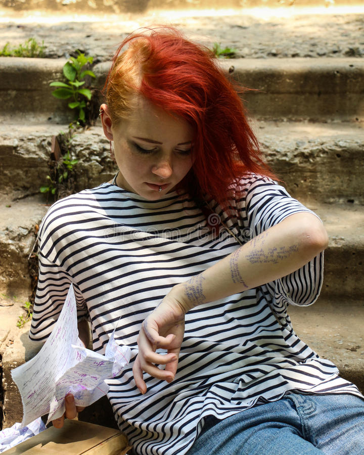 Το κορίτσι με την κόκκινη συνεδρίαση τρίχας στα σκαλοπάτια Εξαπατήστε το φύλλο Φύλλο παχνιών τσαλακωμένο έγγραφο στοκ εικόνες