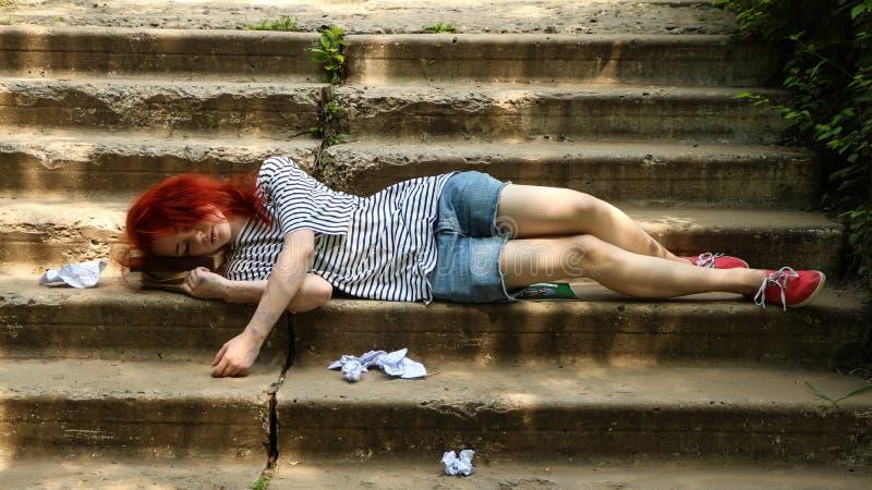 Το κορίτσι με την κόκκινη συνεδρίαση τρίχας στα σκαλοπάτια Εξαπατήστε το φύλλο Φύλλο παχνιών τσαλακωμένο έγγραφο στοκ εικόνα