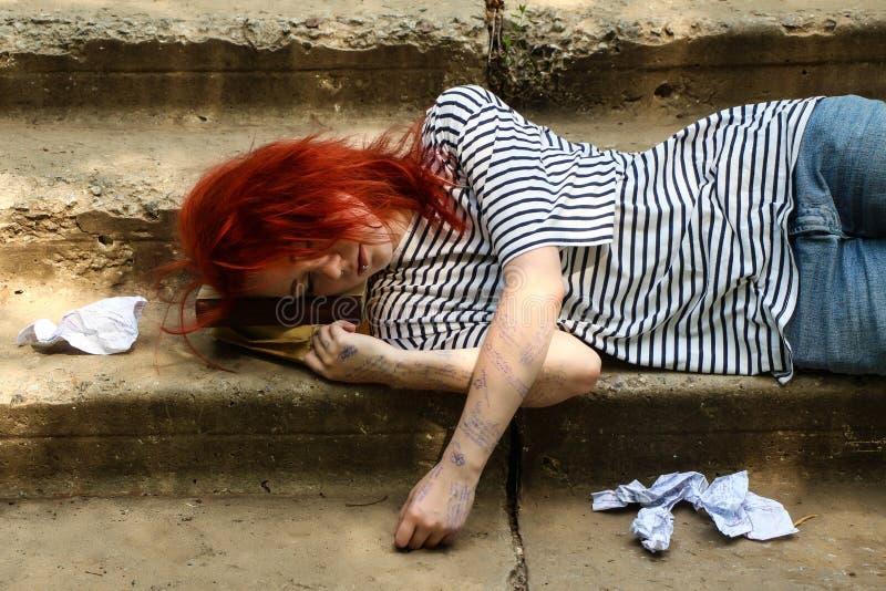 Το κορίτσι με την κόκκινη συνεδρίαση τρίχας στα σκαλοπάτια Εξαπατήστε το φύλλο Φύλλο παχνιών τσαλακωμένο έγγραφο στοκ φωτογραφία με δικαίωμα ελεύθερης χρήσης