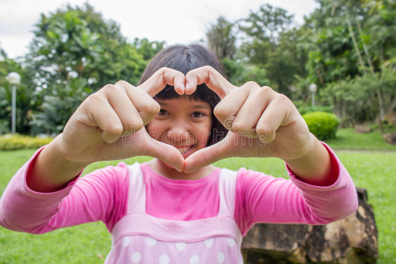 Το κορίτσι με την παραδίδει τη μορφή καρδιών στοκ φωτογραφίες