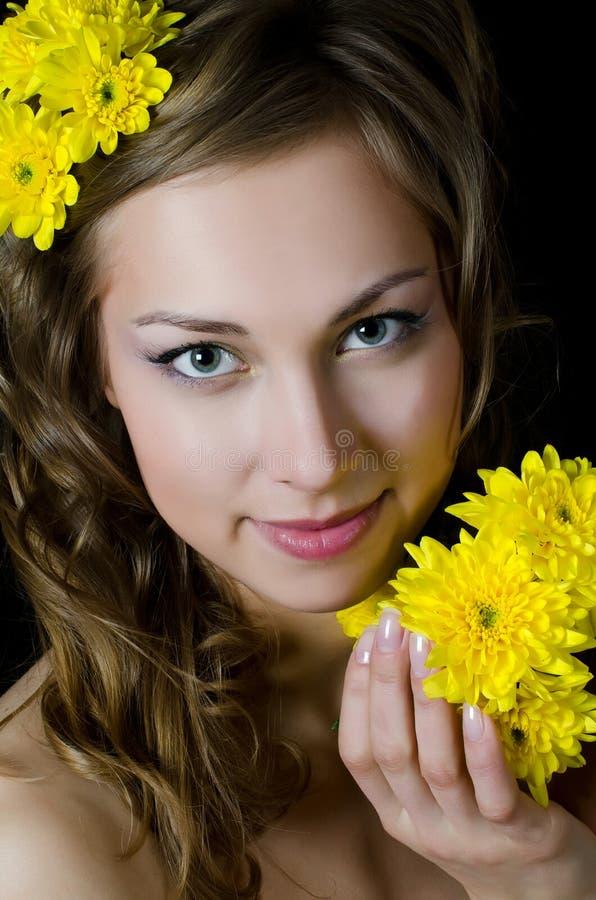 Το κορίτσι με την όμορφη τρίχα με το κίτρινο χρυσάνθεμο στοκ εικόνα