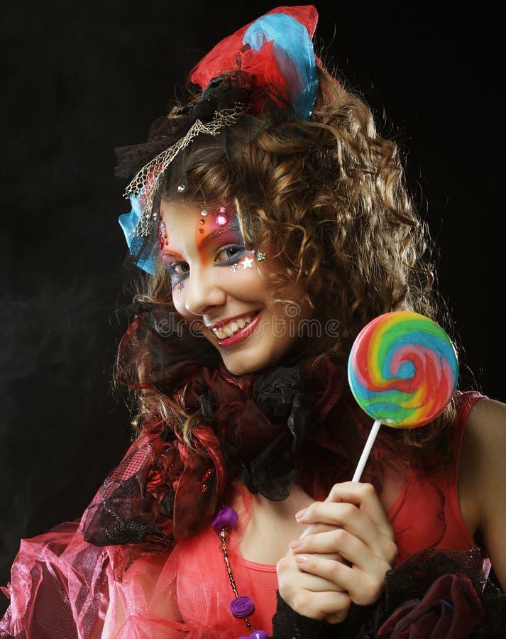 Το κορίτσι με με τη δημιουργική σύνθεση κρατά lollipop Ύφος κουκλών στοκ φωτογραφία