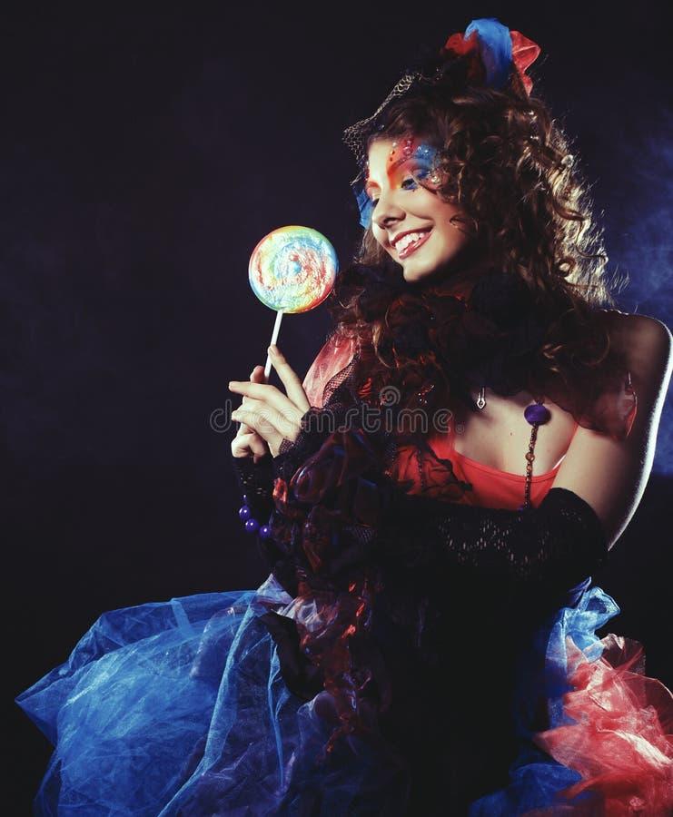 Το κορίτσι με με τη δημιουργική σύνθεση κρατά lollipop Ύφος κουκλών στοκ εικόνα