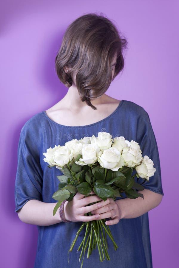Το κορίτσι με τη νυφική ανθοδέσμη στα χέρια της στοκ φωτογραφία
