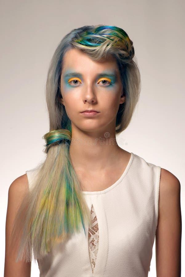 Το κορίτσι με τον επαγγελματικό χρωματισμό τρίχας και δημιουργικός αποτελεί στο ύφος peacock στοκ εικόνα