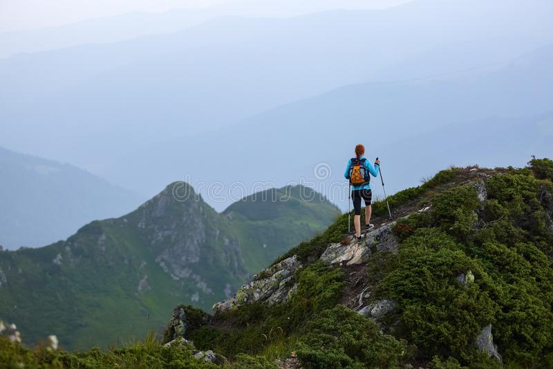Το κορίτσι με τον τουριστικό εξοπλισμό πηγαίνει επάνω στην αιχμή του δύσκολου υψηλού λόφου με το χορτοτάπητα Το τοπίο των βουνών στοκ εικόνα