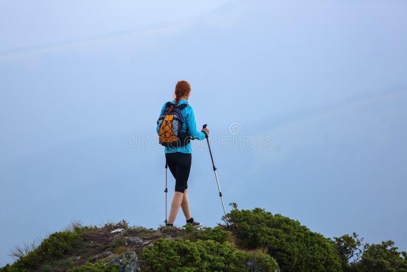 Το κορίτσι με τον τουριστικό εξοπλισμό πηγαίνει επάνω στην αιχμή του δύσκολου υψηλού λόφου με το χορτοτάπητα Το τοπίο του βουνού στοκ εικόνα