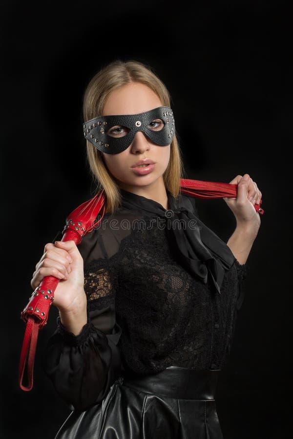 Το κορίτσι με το κόκκινο δέρμα κτυπά και καλύπτει BDSM στοκ εικόνες
