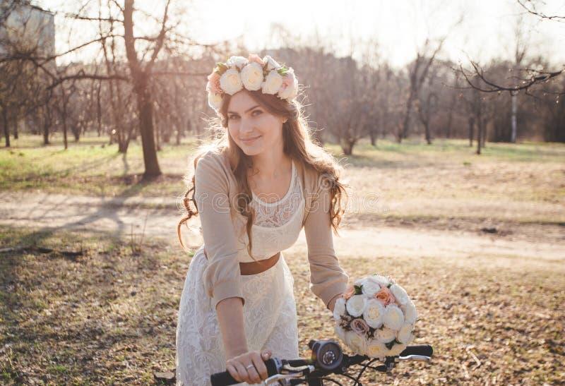 Το κορίτσι με το στεφάνι στο κεφάλι με το ποδήλατο στοκ εικόνες