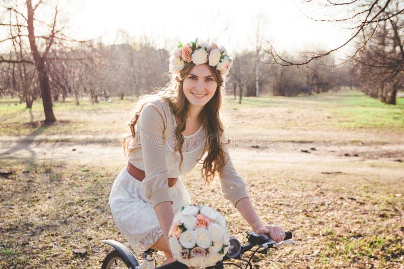 Το κορίτσι με το στεφάνι στο κεφάλι με το ποδήλατο στοκ φωτογραφία με δικαίωμα ελεύθερης χρήσης
