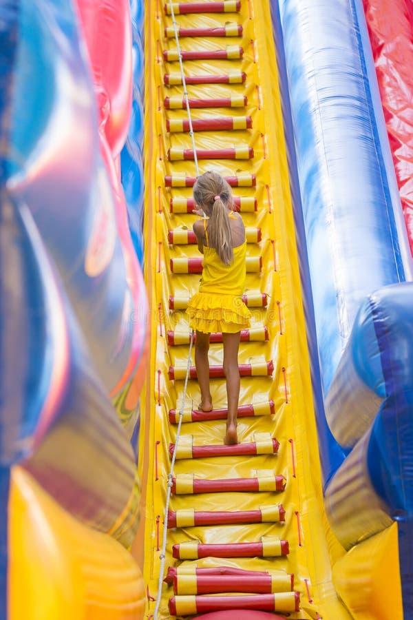 Το κορίτσι με το σχοινί αναρριχείται σε έναν υψηλό λόφο στο τραμπολίνο στοκ εικόνες