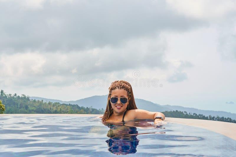 Το κορίτσι μιγάδων στα γυαλιά με τα afrocos κολυμπά στη λίμνη στοκ εικόνα